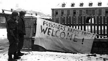 "Eine Leintuch der Amerikaner mit der Aufschrift ""Prisoners Happy End! WELCOME!"" in Flossenbürg 