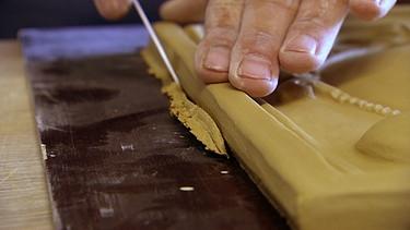 Eine neue Kachel für den Ofen, geformt von Keramikerin Judith Smetana | Bild: BR/Volker Gabriel