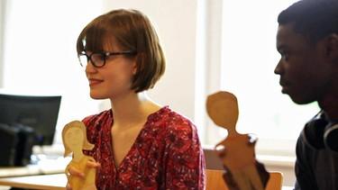 Fiona und Kenny im Deutschkurs erklärend mit den Puppen | Bild: BR