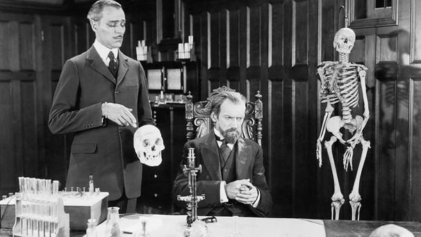 Auf eniem schwarz-weißen Bild sind zwei Wissenschaftler neben Skeletten und Reagenzgläsern zu sehen und scheinen uneins zu sein | Bild: picture alliance / Everett Collection/Old Visuals
