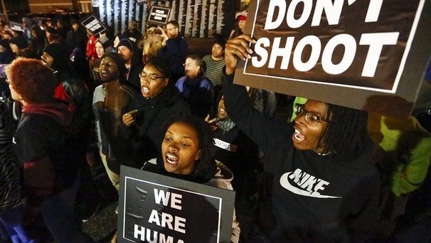 A file photo dated 10 October 2014 of people taking to the street protesting the recent police shootings of several people, outside the Ferguson Police Department headquarters in Ferguson, Missouri, USA.  | Bild: dpa-Bildfunk