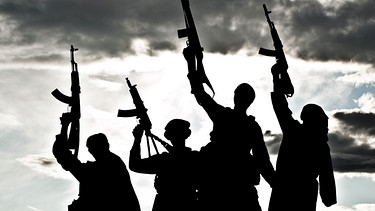 Die Umrisse von mehreren Terroristen vor einem wolkenverhangenen Himmel | Bild: colourbox.com