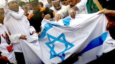 Indonesian activists burn a Israel national flag during a protest against Israel's deadly attack on Gaza-bound humanitarian aid flotilla in Surabaya, East Java, Indonesia, 04 June 2010. Hundreds of protesters continue protests condemning Israel's raid against a pro-Palestinian aid flotilla. EPA/FULLY HANDOKO  +++(c) dpa - Bildfunk+++ | Bild: picture alliance / dpa