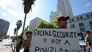 epa02949188 Charles Poper holds a sign that reads 'Social Security is not a Ponzi Scheme' as he joined hundreds of other demontrators in downtown Los Angeles, California, USA 03 October 2011. Hundreds of demonstrators are camping out in Los Angeles as part of a nationwide protest against tax breaks and other government policies towards banks and big corporations and as well as social entitlement programs that some politicians are calling to reforms. EPA/MIKE NELSON  +++(c) dpa - Bildfunk+++ | Bild: Mike Nelson