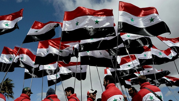 epa03145663 A handout picture released by Syrian Arab News Agency (SANA) shows Syrians waving their national flag during a rally at Umayyad Square in Damascus, Syria, 15 March 2012. Thousands of Syrians loyal to the regime of President Bashar al-Assad gathered on 15 March in the capital Damascus, state media reported. Around one million people are expected to take part in the rally that coincides with the first anniversary of a popular revolt against al-Assad's rule. EPA/SANA / HANDOUT HANDOUT EDITORIAL USE ONLY/NO SALES | Bild: dpa/ picture-alliance