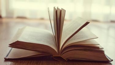 Altes Buch liegt auf einem Tisch | Bild: mauritius images
