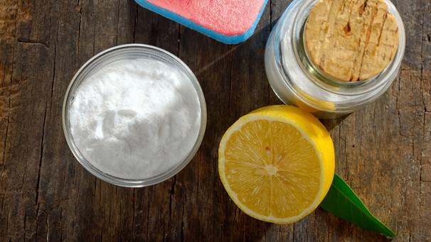 Schälchen Natron steht mit Putzutensilien und Zitrone auf einem Brett | Bild: colourbox.com