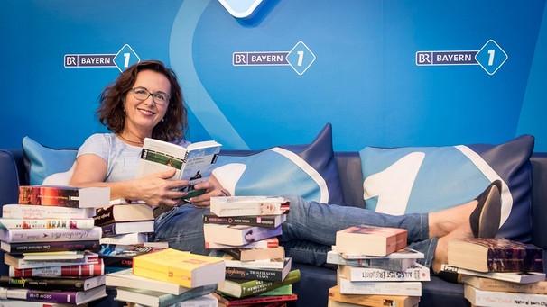 Bayern 1-Moderatorin Ulla Müller liest in einem Stapel voller Bücher | Bild: BR / Philipp Kimmelzwinger
