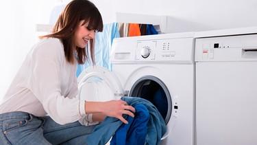 Eine junge Frau gibt Wäsche in die Waschmaschine | Bild: mauritius-images