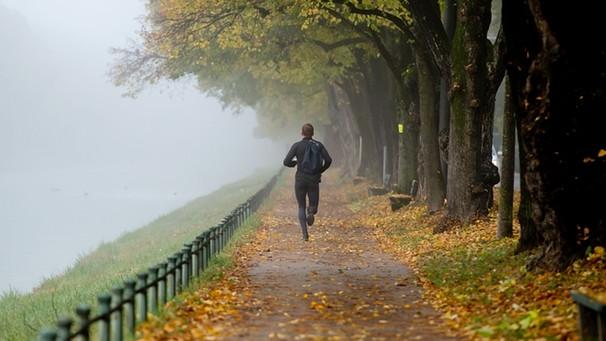 Mann joggt im Nebel an herbstlichen Bäumen entlang / Foto: picture-alliance/dpa
