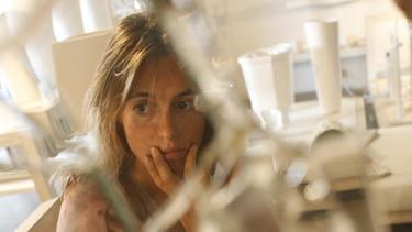 Verängstigte Frau hinter zu Scherben zerborstenem Glas | Bild: colourbox.com