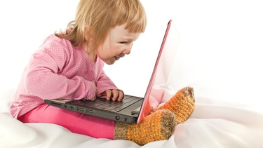 rosarot gekleidetes kleines Mädchen sitzt vor einem Laptop auf dem Bett | Bild: colourbox.com