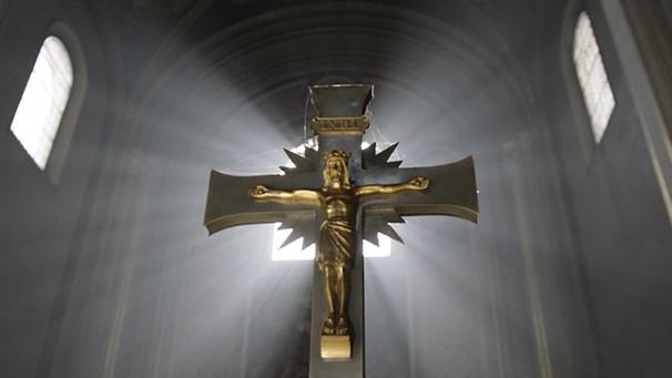 Kreuz vor erleuchtetem Kirchenfenster | Bild: picture-alliance/dpa